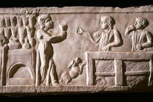 bas relief of romans happily drinking wine in a tavern