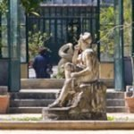 The central greenhouse of the botanic garden of Palermo with a classic statue at the entrance, lush growing plant everywhere