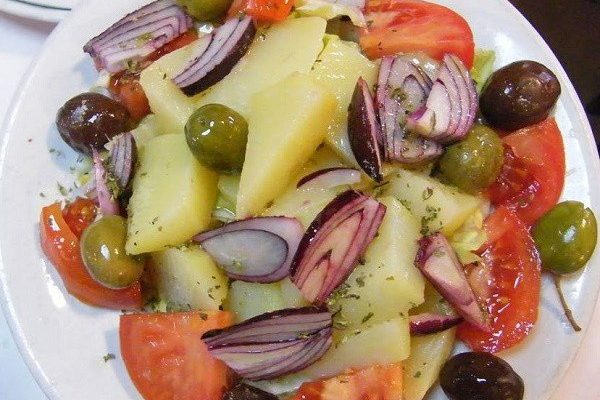 insalata vastasa, all ingredients -potato, tomato, onion and olives - straight from the greengrocer, mixed together and served; simple