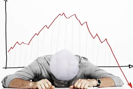 person laying down on desk with failure graph in background